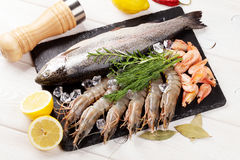Fresh raw sea food with spices. On stone plate over wooden table background. Top view Stock Photography