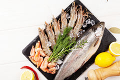 Fresh raw sea food with spices. On stone plate over wooden table background. Top view with copy space Royalty Free Stock Image