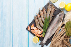 Fresh raw sea food with spices. On stone plate over wooden table background. Top view with copy space Royalty Free Stock Photo