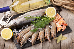 Fresh raw sea food with spices and white wine bottle. Fresh raw sea food with spices and whtie wine bottle on wooden table background Stock Photos