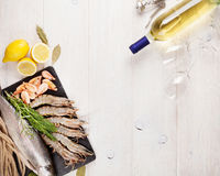 Fresh raw sea food with spices and white wine bottle. Fresh raw sea food with spices and whtie wine bottle on wooden table background. Top view with copy space Stock Image