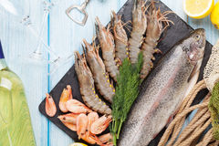 Fresh raw sea food with spices and white wine. On wooden table background. Top view Stock Photo