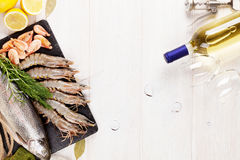 Fresh raw sea food with spices and white wine. On wooden table background. Top view with copy space Stock Photos
