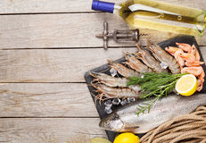 Fresh raw sea food with spices and white wine. On wooden table background. Top view with copy space Stock Image