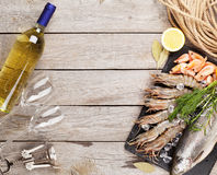 Fresh raw sea food with spices and white wine. On wooden table background. Top view with copy space Royalty Free Stock Photography