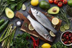 Fresh raw seabass and ingredients for cooking. Rosemary, thyme, lime, lemon, greens and vegetables. Top view Royalty Free Stock Photos
