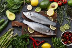 Fresh raw seabass and ingredients for cooking stock image