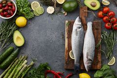 Fresh raw seabass and ingredients for cooking. Rosemary, thyme, lime, lemon, greens and vegetables. Top view, copyspace Stock Photos