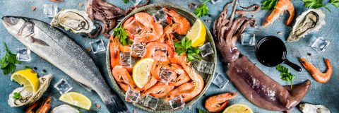 Fresh raw seafood. Squid shrimp oyster mussels fish with spices of herbs lemon on a light blue background copy space top view  banner Stock Photo