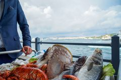 Fresh raw seafood presentation on cart at seaside restaurant by a man in suit including fishes, prawn, shell, etc. On blurred ocean and sky background Royalty Free Stock Image
