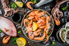 Fresh raw seafood. Squid shrimp oyster mussels fish with spices of herbs lemon on dark rusty background copy space top view Royalty Free Stock Photography