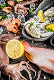 Fresh raw seafood. Squid shrimp oyster mussels fish with spices of herbs lemon on dark rusty background copy space top view Stock Photo