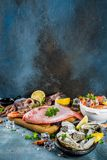 Fresh raw seafood. Squid shrimp oyster mussels fish with spices of herbs lemon on a light blue background copy space Royalty Free Stock Photo