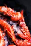 Fresh raw shrimps on black background with ice - Food background Stock Photo