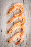 Fresh raw shrimps. Four fresh raw shrimps on wooden table. Top view Royalty Free Stock Photography