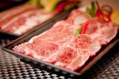 Fresh raw sliced beef with chili on black tray.  Royalty Free Stock Image