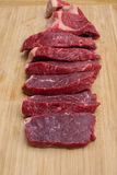 Fresh raw sliced meat beef on an wooden cutting board. Top view of fresh raw sliced meat beef on an wooden cutting board. Selective focus. Vertical images Stock Photo