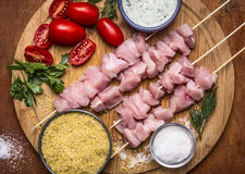 Fresh raw sliced turkey breast on skewer  with bulgur, with tomato sauce and herbs with salt on a cutting board on a wooden backgr Royalty Free Stock Photos