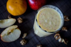 Fresh raw smoothie with apples, oranges, banana and walnuts on the dark background. Fresh raw smoothie with apples, oranges, banana and walnuts on the dark Royalty Free Stock Image