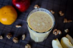 Fresh raw smoothie with apples, oranges, banana and walnuts on the dark background. Fresh raw smoothie with apples, oranges, banana and walnuts on the dark Royalty Free Stock Photos