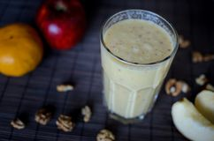 Fresh raw smoothie with apples, oranges, banana and walnuts on the dark background. Fresh raw smoothie with apples, oranges, banana and walnuts on the dark Stock Photos