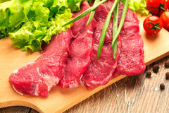 Fresh, raw stakes from meat veal on a wooden chopping board with setion. Fresh, crude stakes from meat veal on a wooden chopping board with setion, black pepper Stock Images