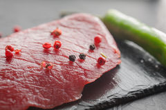Fresh raw steak with chili on black stone Royalty Free Stock Image