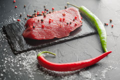 Fresh raw steak with chili on black stone Royalty Free Stock Images