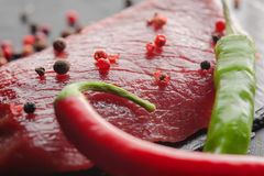 Fresh raw steak with chili on black stone Stock Photo
