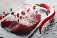 Fresh raw steak with chili on black stone Royalty Free Stock Photo