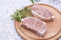 Fresh Raw Steak Meat with spaces, herbs and vegetables. On wooden board royalty free stock photography