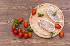 Fresh Raw Steak Meat with spaces, herbs and vegetables on wooden board. Selective focus Stock Image