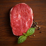 Fresh raw steak with pepper and basil. On the wooden board Stock Images