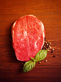 Fresh raw steak with pepper and basil. On the wooden board.Filtered image: warm cross processed vintage effect.n Stock Image