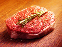 Fresh raw steak with pepper and rosemary. On the wooden board.Filtered image: warm cross processed vintage effect Stock Photos