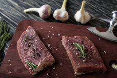 Fresh raw steaks with rosemary and garlic on wooden desk. Fresh raw steaks with rosemary and garlic on the desk Stock Photography