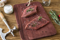 Fresh raw steaks with rosemary and garlic on wooden desk. Fresh raw steaks with rosemary and garlic on the desk Stock Photo