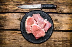 Fresh raw steaks on a stand and carving knife. On wooden background. Top view Royalty Free Stock Images