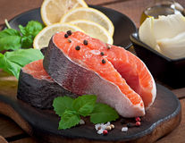 Fresh and raw steaks trout on a wooden cutting board. With sliced lemon, basil and pepper Stock Photo