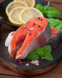 Fresh and raw steaks trout on a wooden cutting board. With sliced lemon, basil and pepper Stock Images