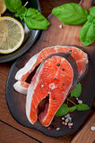 Fresh and raw steaks trout on a wooden cutting board. With sliced lemon, basil and pepper Royalty Free Stock Image