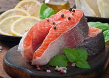 Fresh and raw steaks trout on a wooden cutting board. With sliced lemon, basil and pepper Royalty Free Stock Photos