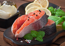 Fresh and raw steaks trout on a wooden cutting board. With sliced lemon, basil and pepper Royalty Free Stock Images