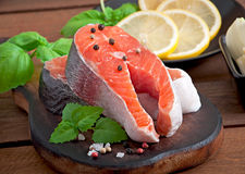 Fresh and raw steaks trout on a wooden cutting board. With sliced lemon, basil and pepper Stock Photography