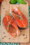 Fresh and raw steaks trout on a wooden cutting board. With sliced lemon, rosemary and pepper Royalty Free Stock Photos
