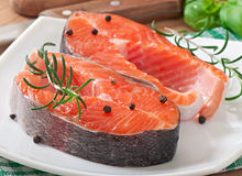 Fresh and raw steaks trout on a wooden cutting board. With sliced lemon, rosemary and pepper Stock Image