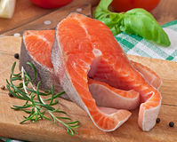Fresh and raw steaks trout on a wooden cutting board. With sliced lemon, rosemary and pepper Stock Photos