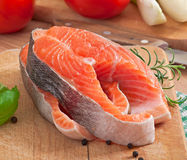 Fresh and raw steaks trout on a wooden cutting board. With sliced lemon, rosemary and pepper Royalty Free Stock Photo