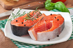 Fresh and raw steaks trout on a wooden cutting board. With sliced lemon, rosemary and pepper Royalty Free Stock Image