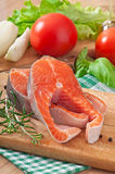 Fresh and raw steaks trout on a wooden cutting board. With sliced lemon, rosemary and pepper Stock Photo